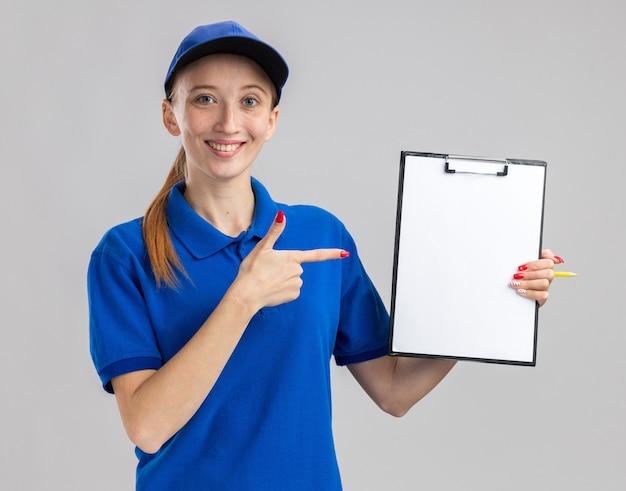 Молодая доставщица в синей форме и кепке держит буфер обмена с пустыми страницами, указывая на него указательным пальцем, уверенно улыбаясь