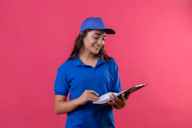 ピンクの背景の上に自信を持って立っている笑顔でそれを見てペンで青い制服とキャップを持ってクリップボードの若い配達の少女
