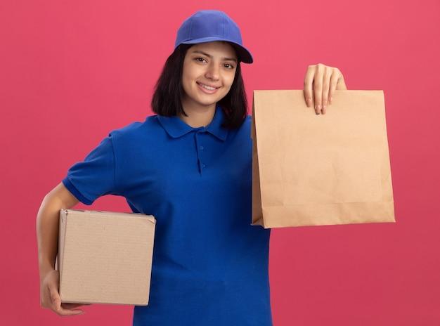 Молодая доставщица в синей форме и кепке держит бумажный пакет и картонную коробку, улыбаясь счастливым лицом, стоя над розовой стеной