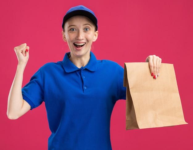 Молодая доставщица в синей форме и кепке держит бумажный пакет, счастливая и взволнованная сжимая кулак