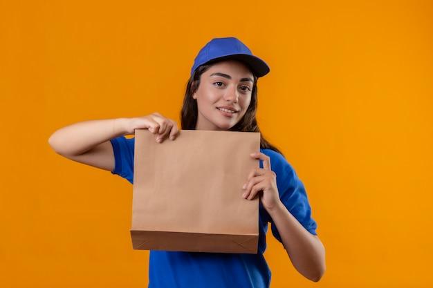青い制服を着た若い配達少女と黄色の背景の上にフレンドリーな立っている笑顔のカメラを見て紙のパッケージを保持しているキャップ