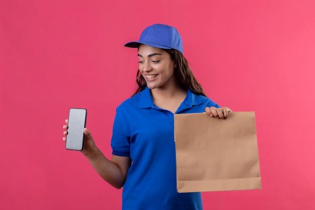 ピンクの背景の上に元気に立って笑っているそれを見てスマートフォンを示す青いユニフォームとキャップを保持している紙のパッケージの若い配達の少女