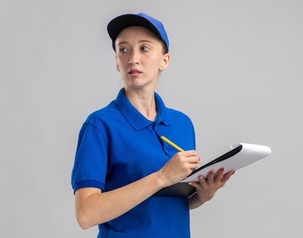 青い制服を着た若い配達の女の子と、白い壁の上に立って何かを書いている真剣な顔でよそ見の空白のページで鉛筆とクリップボードを保持しているキャップ