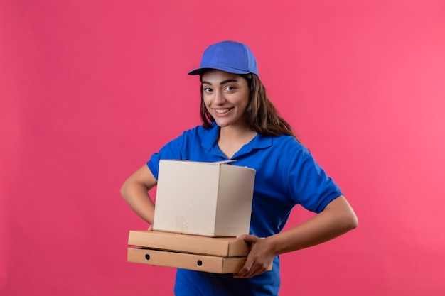 Молодая доставщица в синей униформе и кепке держит коробки для пиццы и коробку, глядя в камеру, весело улыбаясь и радостно улыбаясь на розовом фоне