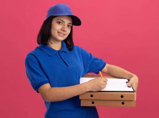 파란색 제복을 입은 젊은 배달 소녀와 분홍색 벽 위에 서있는 얼굴에 미소로 펜으로 피자 상자와 클립 보드를 들고 모자
