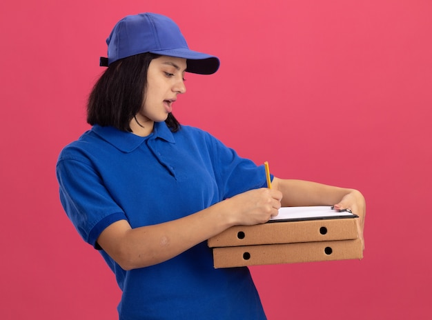 ピンクの壁の上に立っている深刻な顔で何かを書いているピザの箱とクリップボードを保持している青い制服と帽子の若い配達の女の子