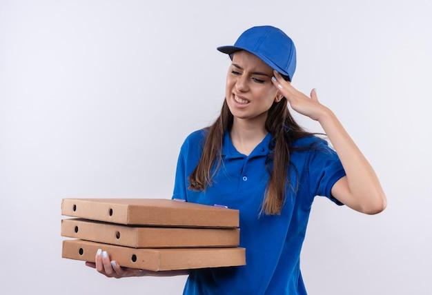 Молодая доставщица в синей униформе и кепке держит коробки для пиццы, выглядит усталой и перегруженной, трогает голову, чувствуя боль