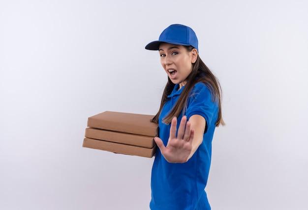 Молодая доставщица в синей форме и кепке держит коробки для пиццы, делая знак остановки рукой с выражением страха на лице