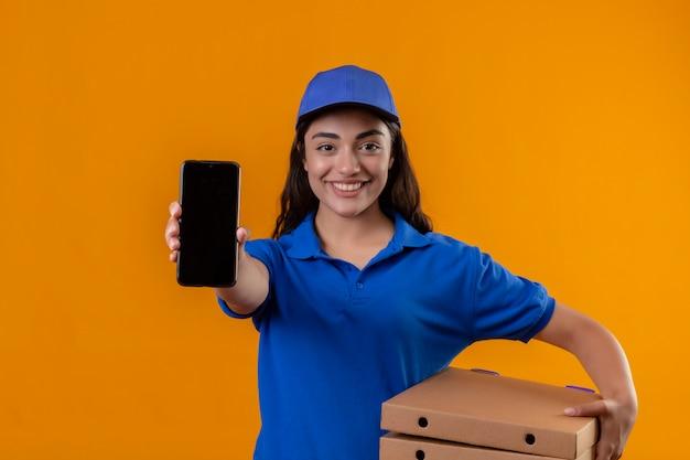 Молодая доставщица в синей форме и кепке держит коробки для пиццы, показывая смартфон в камеру, дружелюбно улыбаясь, стоя на желтом фоне