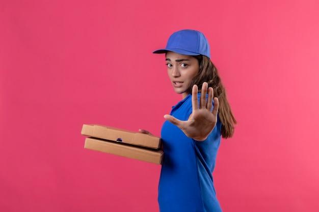 Молодая доставщица в синей форме и кепке держит коробки для пиццы, стоя с открытой рукой, делая знак остановки с серьезным и уверенным жестом защиты на розовом фоне