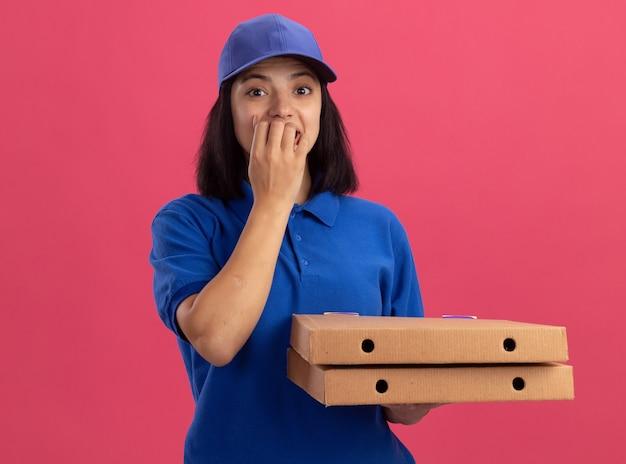 青いユニフォームとピザの箱を保持しているキャップの若い配達の女の子は、ピンクの壁の上に立っている彼女の爪を噛んでストレスと神経質になりました