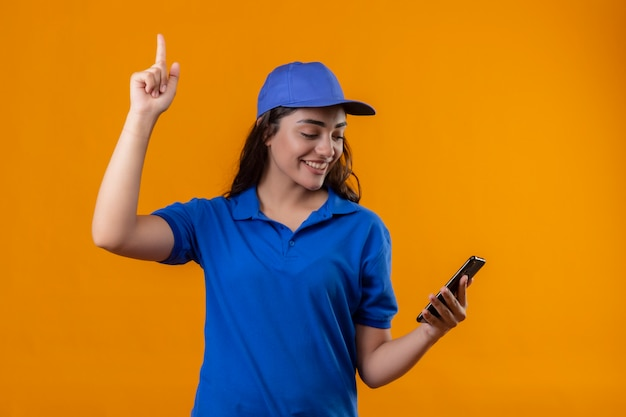 파란색 제복을 입은 젊은 배달 소녀와 모자를 손에 들고 스마트 폰을 손에 들고 노란색 배경 위에 자신감이 서있는 미소 짓는 좋은 아이디어가있는 손가락을 가리키는 손가락