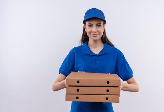 파란색 유니폼과 모자에 젊은 배달 소녀 얼굴에 자신감이 미소로 카메라를 찾고 피자 상자 스택을 들고