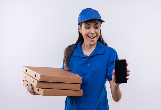 Молодая доставщица в синей форме и кепке держит стопку коробок для пиццы, показывая смартфон весело улыбаясь