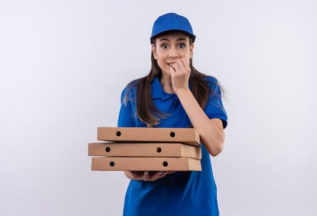 青いユニフォームとピザの箱のスタックを保持しているキャップの若い配達の女の子は、ストレスと神経質な刺すような爪