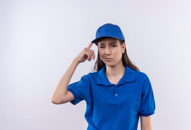 青いユニフォームとキャップを着た若い配達の女の子がカメラを見て混乱し、彼女の寺院を間違って指さし、忘れました