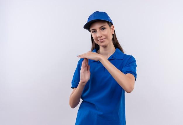 Молодая доставщица в синей форме и кепке смотрит в камеру, делая тайм-аут руками