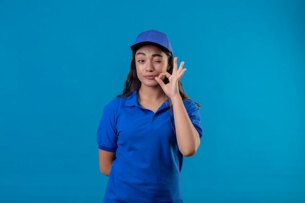 파란색 제복을 입은 젊은 배달 소녀와 파란색 배경 위에 서있는 지퍼로 그녀의 입을 닫는 것처럼 윙크하는 침묵 제스처를 만드는 카메라를보고 모자