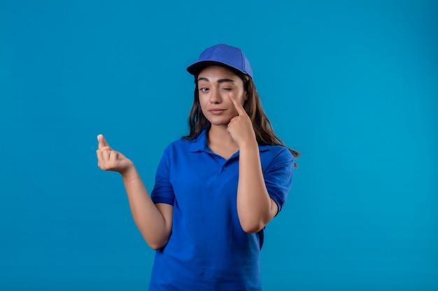 파란색 유니폼과 모자 돈 제스처를 만드는 젊은 배달 소녀 파란색 배경 위에 지불 서를 기다리는 그녀의 눈에 카메라를 가리키는 손가락을보고 자신감 미소