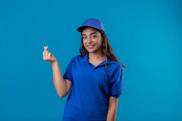 Молодая доставщица в синей форме и кепке делает денежный жест, уверенно улыбаясь, глядя в камеру, стоящую на синем фоне