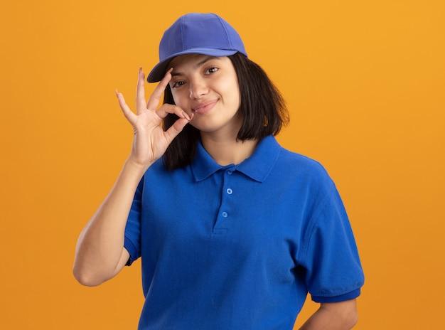 Молодая доставщица в синей форме и кепке делает жест молчания, словно закрывает рот на молнии, стоит над оранжевой стеной