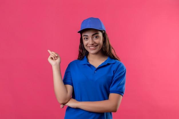青い制服を着た若い配達の少女とピンクの背景の上に自信を持って幸せと肯定的な立っている笑顔側に指で指しているキャップ
