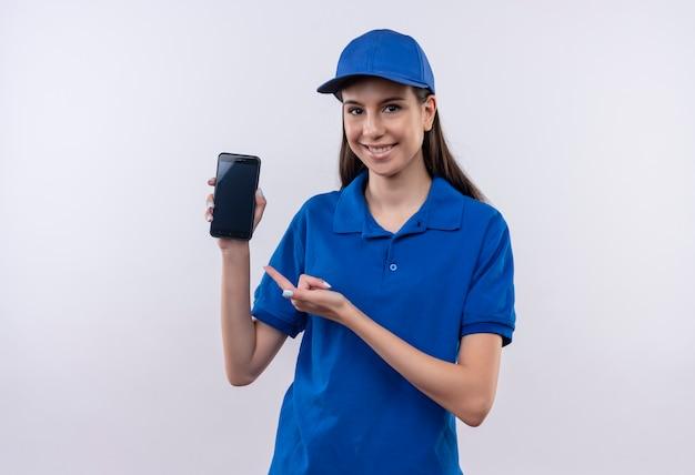 파란색 제복을 입은 젊은 배달 소녀와 얼굴에 미소로 카메라를보고 스마트 폰을 제시하는 모자