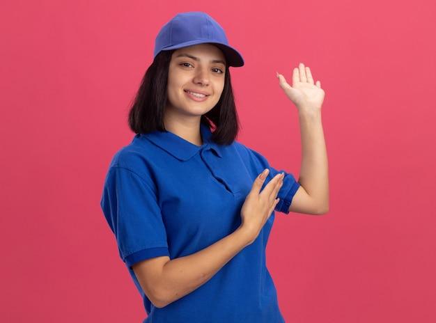 파란색 제복을 입은 젊은 배달 소녀와 팔을 제시하는 모자 오 손이 분홍색 벽 위에 유쾌하게 서서 웃고