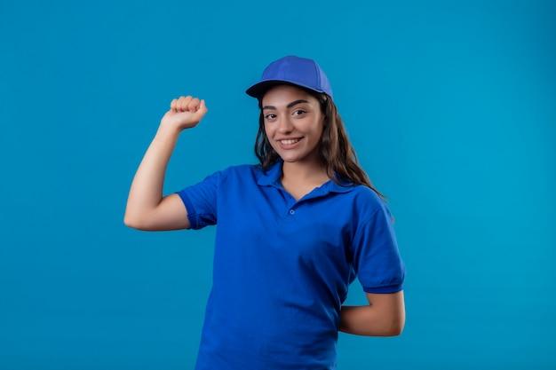 青い制服を着た若い配達の女の子と自信を持って彼女の成功と青い背景の上に立って勝利立って笑って自信を持ってカメラを見て拳を上げるキャップ