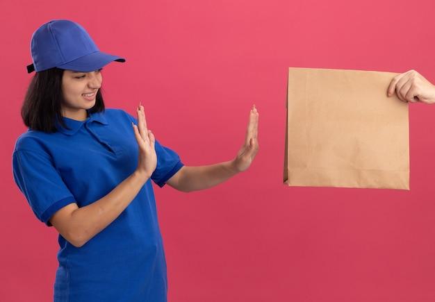 파란색 제복을 입은 젊은 배달 소녀와 분홍색 벽 위에 서있는 종이 패키지를 거부하는 모자