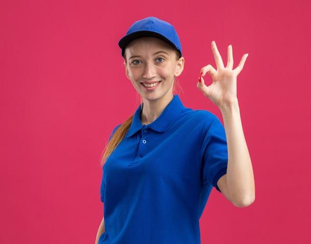 Молодая доставщица в синей форме и кепке, уверенно улыбаясь, делает хорошо, знак стоит над розовой стеной