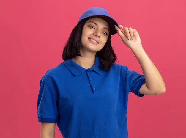 파란색 제복을 입은 젊은 배달 소녀와 모자는 분홍색 벽 위에 서있는 그녀의 모자를 고정하는 자신감을 웃고