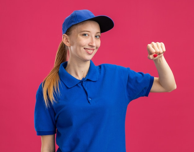 Молодая доставщица в синей форме и кепке улыбается уверенно, счастлива и позитивно показывает кулак, стоящий над розовой стеной