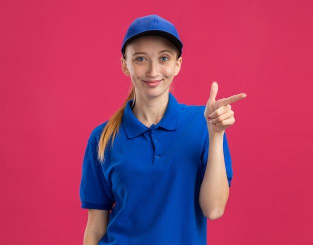 Молодая доставщица в синей форме и кепке дружелюбно улыбается, указывая указательным пальцем в сторону, стоя над розовой стеной