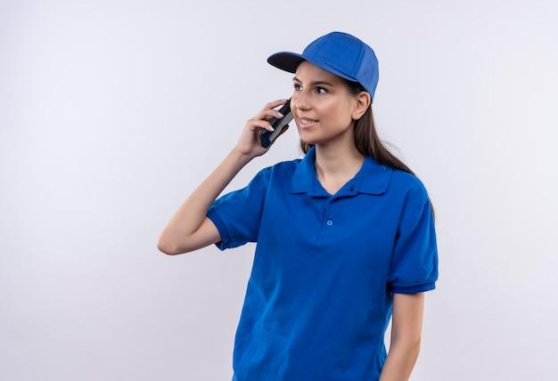 파란색 제복을 입은 젊은 배달 소녀와 모자는 휴대 전화로 이야기하는 동안 웃고