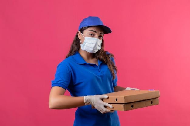 Молодая доставщица в синей форме и кепке, в защитной маске и перчатках, держит коробки с пиццей и смотрит в камеру с серьезным уверенным выражением лица, стоя на розовом фоне