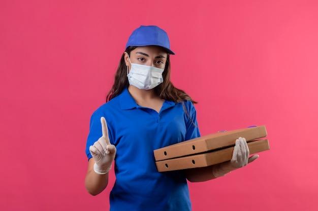 Молодая доставщица в синей форме и кепке в защитной маске и перчатках держит коробки с пиццей, указывая пальцем вверх, предупреждающий жест, глядя в камеру с серьезным лицом, стоящим над пи
