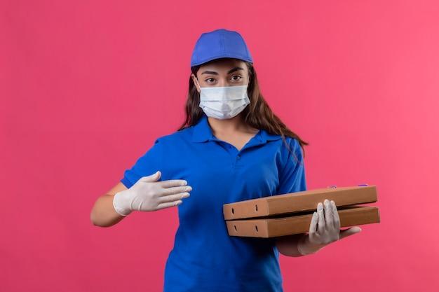 Молодая доставщица в синей униформе и кепке в защитной маске для лица и перчатках держит коробки для пиццы, указывая рукой, уверенно глядя, стоя на розовом фоне