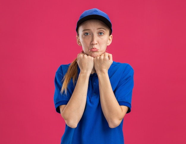 Молодая доставщица в синей форме и кепке с грустным выражением лица, поджимая губы