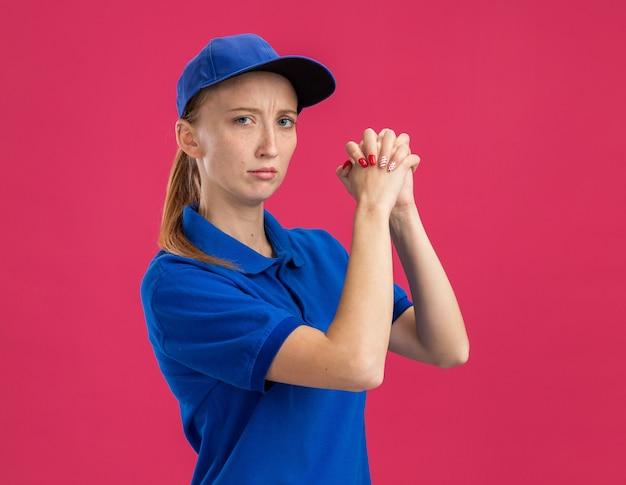 Молодая доставщица в синей форме и кепке с серьезным уверенным выражением лица держится за руки вместе, делая жест совместной работы, стоя над розовой стеной