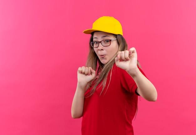 赤いポロシャツと黄色い帽子の若い配達の女の子が終了し、幸せな握りこぶしが踊る