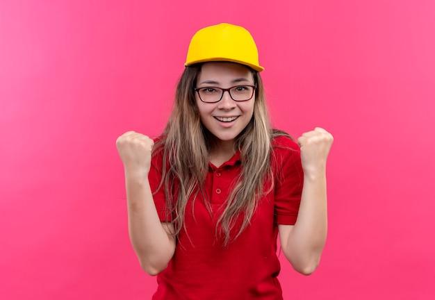 赤いポロシャツと黄色い帽子の若い配達の女の子が出て、幸せな握りこぶし