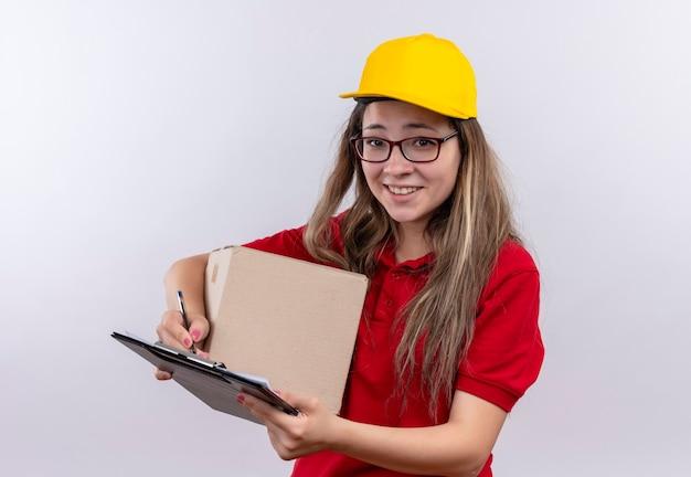 恥ずかしがり屋の笑顔でカメラを見て赤いポロシャツと黄色の帽子保持ボックスパッケージとクリップボードの若い配達の女の子