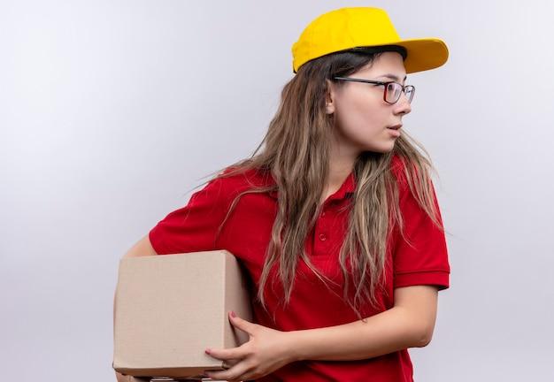 真面目な顔で脇を見て赤いポロシャツと黄色の帽子保持ボックスパッケージの若い配達の女の子