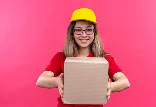 自信を持って笑顔のカメラを見て赤いポロシャツと黄色の帽子保持ボックスパッケージの若い配達の女の子