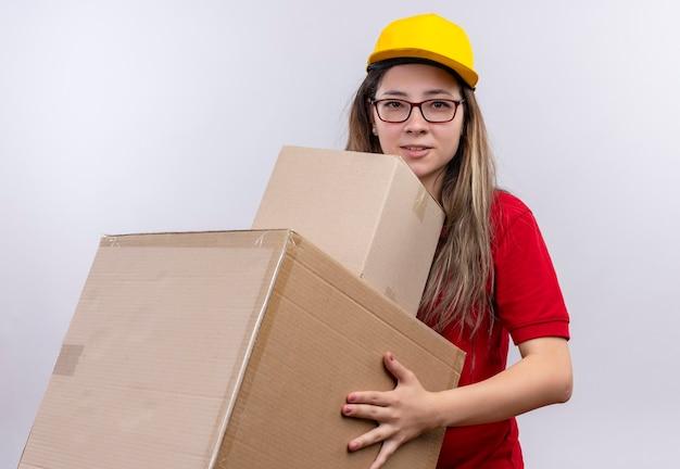 顔に自信を持って笑顔でカメラを見て段ボール箱を保持している赤いポロシャツと黄色の帽子の若い配達の女の子