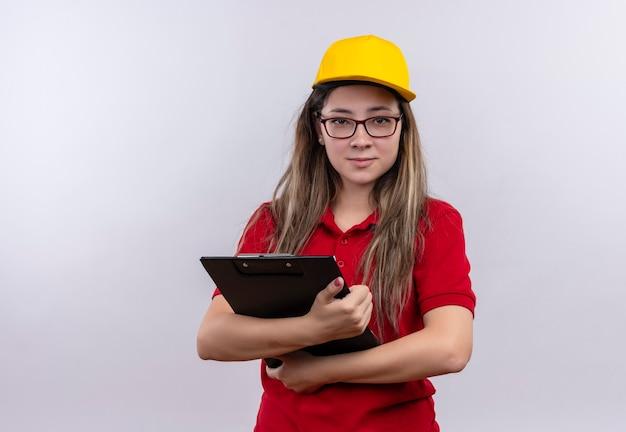 自信を持って見えるクリップボードを保持している赤いポロシャツと黄色の帽子の若い配達の女の子