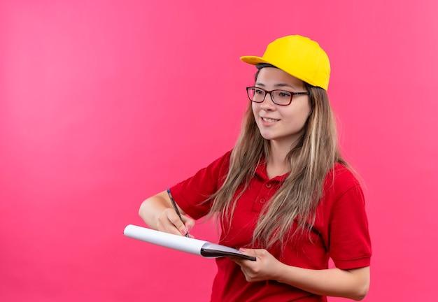 赤いポロシャツと空白の笑顔でクリップボードを保持している黄色の帽子の若い配達の女の子