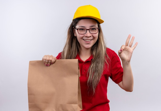 赤いポロシャツと黄色い帽子の若い配達の女の子が元気にokサインを示して笑っている紙のパッケージを保持
