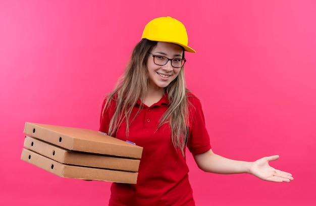 広く笑っているピザの箱を保持している赤いポロシャツと黄色の帽子の若い配達の女の子